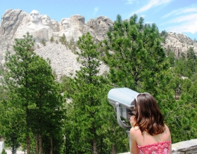 Girl Looking At Mount Rushmore National Memorial Through Binoculars
